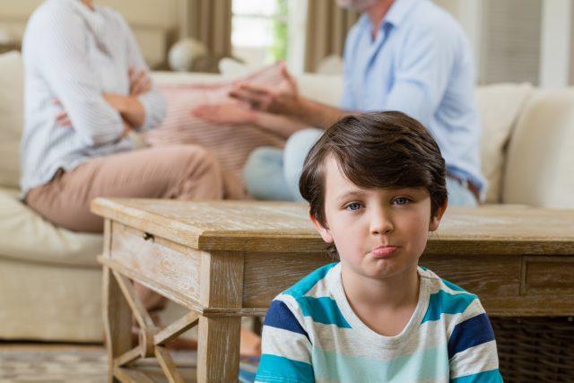 Smutný chlapec poslouchá hádku rodičů